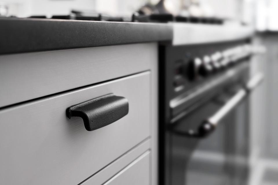 Litinová úchytka ART of firmy Furnipart namontovaná v kuchyni na bílém čílku dokresluje atmosféru.